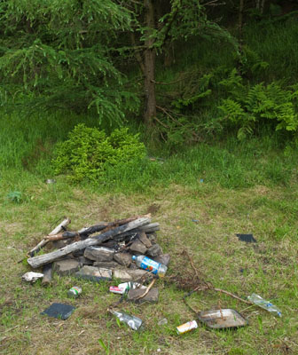 An illegal campfire surrounded by rubbish.